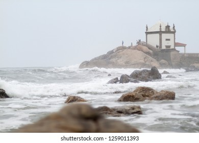 A view to oceanfront chapel built on rocks Senhor da Pedra from the ocean in Miramar, Portugal