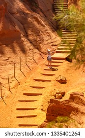 """View of the ocher land and people walking the stairs, woman taking pictures, in the park """"Sentiers des Ocres"""" near the village of Roussillon, Vaucluse, Provence, France. Vertical photo. Travel France."""
