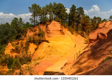 """View of the ocher land and a woman climbing the mountain in the park """"Sentiers des Ocres"""" near the village of Roussillon, Vaucluse, Provence, France. Holidays in France."""
