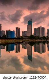 A view of office buildings in Jakarta at dusk under an overcast sky