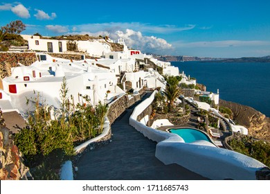 View of Oia city in sunny weather. The background is a blue sky with white clouds. City on Santorini island in Greece.
