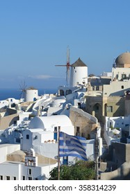 View of Oia, Santorini with Greek flag flying in foregrown