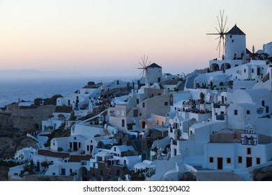 View of Oia Village with windmills at sunset, Santorini, Greece