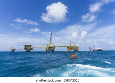 View oil and gas plaform with accommodation work barge in the middle of the sea. View taken from stern vessel with blue sky and blue sea. Buoyancy tank floating near the vessel.