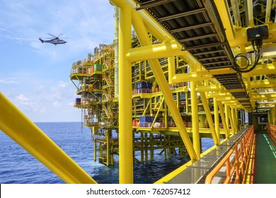 View of oil and gas platform in the middle of the sea with background blue sky and helicopter approaching to helideck.
