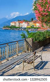 View of old Bellagio town and path along beautiful Como lake, Italy. Nature scenery with blossoming tree. Como lake landscape.