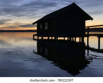 """View of an old boathouse at the lake """"Ammersee"""" and near the Alps in Bavaria in the wintertime"""