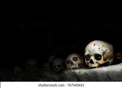 view of an old, cracked and damaged human skull on the dark shelves of the crypt. death, appocalypstic concept, cannibalism,