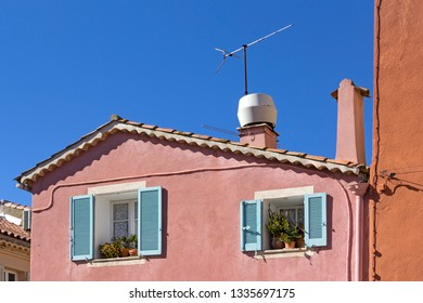 View of an old facade with two windows. Seen in France, in Sainte Maxime, French Riviera.