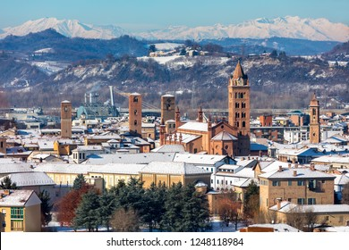 View of old historic center of Alba  with cathedral and medieval towers covered with snow in Piedmont, Northern Italy.