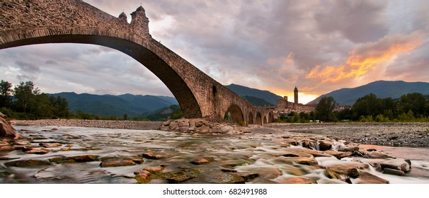 """View of the old medieval bridge, called """"Ponte del Diavolo"""" or """"Ponte Gobbo"""" over the river Trebbia in the small town of Bobbio (northern Italy)"""