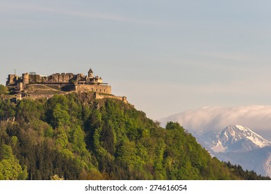 View of the old medieval castle of Landskron in Villach/Austria, located on top of a hill surrounded by a forest, in front of the Karawanks Mountains including prominent Mt. Kepa