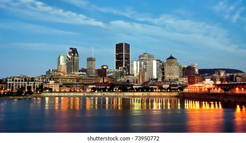 View of Old Montreal with a portion of the port, and office buildings in background at dusk.