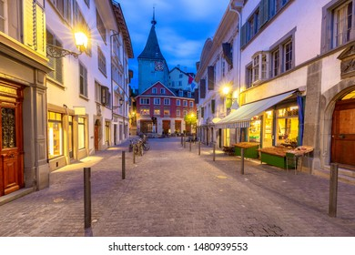 View of the old narrow medieval city street with burning lanterns. Zurich. Switzerland.