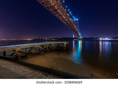View of an old pier in the banks of the Tagus River (Rio Tejo) with the 25 of April Bridge on the backgound at night; Concept for visit Lisbon and most beaufiful places in Portugal