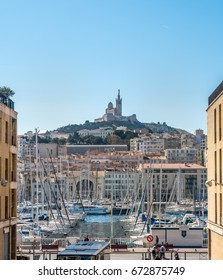 View of old port of Marseille and Basilica of Our Lady of Guard catholic church (Notre-Dame de la Garde) from street to the port in Marseille, France