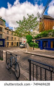 View of old street with old mill and bike in quarter Montmartre in Paris, France. Cozy cityscape of Paris. Architecture and landmarks of Paris.
