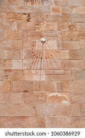 View of an old sundial located on an ancient wall. Roman numbers written on the rectangular board.