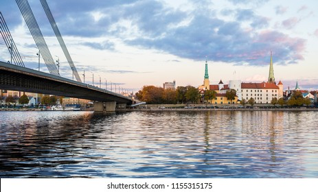 View of the Old Town and the cable-stayed bridge from the promenade of the Daugava river at sunset. Riga, Latvia