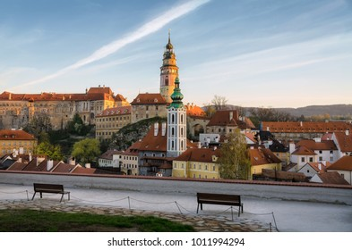View of the old town of Cesky Krumlov from the observation deck. Two benches for tourists stand in the foreground. Czech Krumlov, Czech Republic.