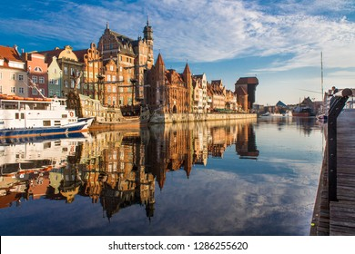 View of old town Gdansk (Gdańsk), Poland (Polska) with merchants' house, Mariacka Gate, and famous historic Medieval Crane. Beautiful morning on the Motlava River. No wind, no people, only one angler.