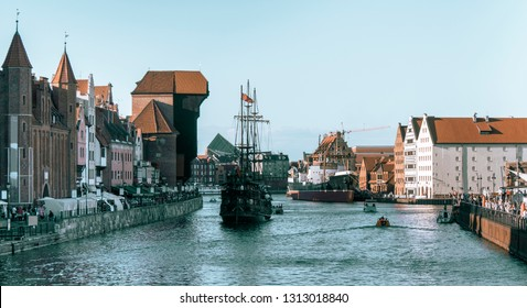 View of old town Gdansk (Gdańsk), Poland (Polska) with, merchants' house, granary, pirate ship, and famous historic Medieval Crane. Crowds of tourist by the Motlava River. Time of the Dominican Fair.