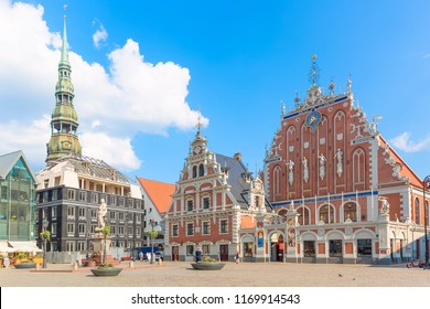 View of the Old Town square, Roland Statue, The Blackheads House and St Peters Cathedral against blue sky in Riga, Latvia. Summer sunny day