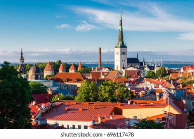 View of the old town of Tallinn from the observation deck. Red tiled roofs, the church of St. Olaf, the Baltic Sea in the background. Card. Estonia.