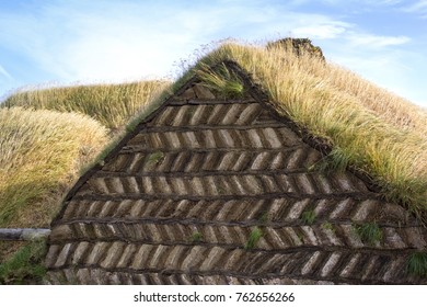 View of an old and traditional village in Iceland. The facade in the foreground is made of peat and sod. The buildings also have a roof made of peat.