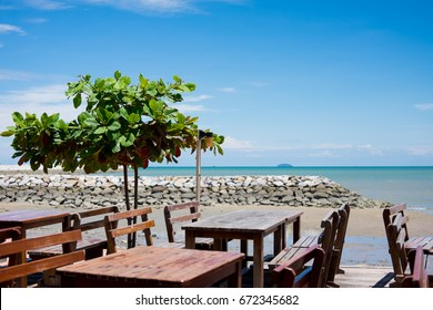 View of old wooden table chairs with rock wave breaker and green tree on seashore with blue sky for leisure background (selective focus)