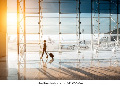 View on the aiport window with woman walking with suitcase at the departure hall during the sunset. Wide angle view with copy space