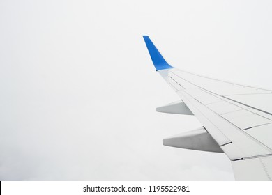 View on airplane wing in the cloudy sky during the flight. Overcast consept, bad visibility.