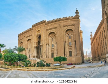 The view on Al-Rifai Mosque, the wall of Sultan Hassan Mosque-Madrasa and the slender minaret of Alabaster (Muhammad Ali) Mosque of Saladin Citadel on the background, Cairo, Egypt.