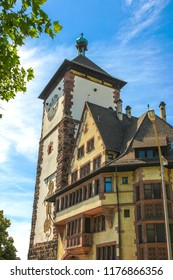 View on the ancient buildings with the Schwabentor clock tower in Freiburg im Breisgau, Germany on a sunny day.