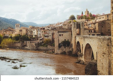view on an ancient old medieval town, a small village with towers bridge from yellow orange bricks in Spain near river and mountains