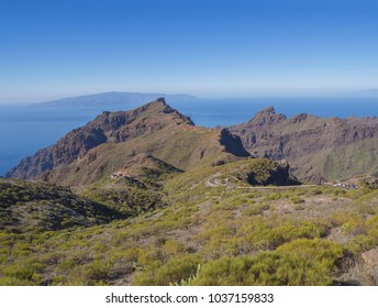 view on asfalt road to village Masca in Tenerife with green hills, sharp mountain peaks, sea horizon and clear blue sky background