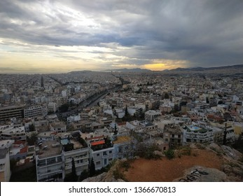 View on Athens city, Greece at sunset with dark clouds
