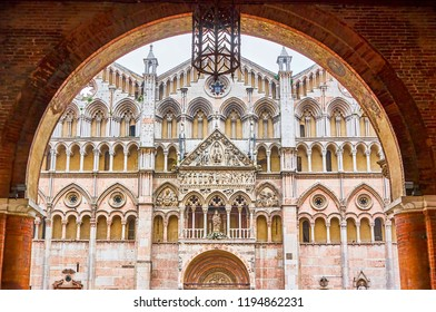 The view on beautiful frontage of Ferrara Duomo from the arch of Palazzo Duches Estense, Italy