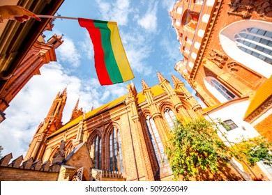 View on the beautiful gothic saint Anna and Francis of Assisi churches eith lithuanian flag in the old town of Vilnius city, Lithuania.