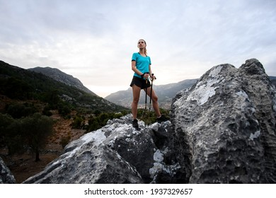 view on beautiful woman tourist with trekking poles standing on large stone against sky in mountains in Turkey