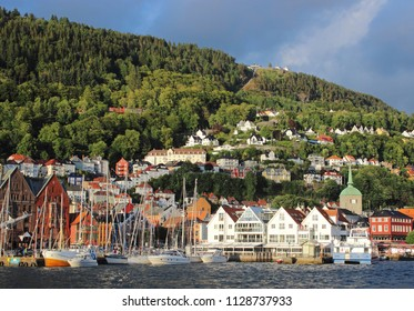 The view on Bergen coast with old houses and boats on summer day. Norway town and mountains landscape.