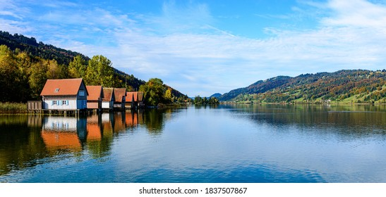 View on big, Grosser Alpsee lake by Immenstadt im in Allgau with wooden hauses, blue sky. Bavaria, Germany. Border with Austria, Vorarlberg. - Shutterstock ID 1837507867
