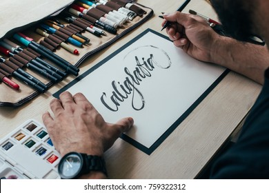 View on big sheet of white paper canvas with word calligraphy spelled on top using brush with black ink by font designer or creative artist freelancer working on project in home studio