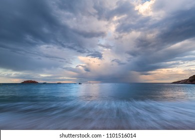 View on blurred sea waves in front and rock islands in distance under stormy sky before sunset in Costa Brava (Spain)
