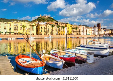 View on the boats on the river Temo, colorful houses and the Castle Malaspina in pier, bridge, clouds, sky, castle walls,Bosa, Sardinia, Italy