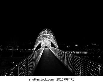 View on bridge of Peace over Kura River (Mtkvari) with neon illuminated at night. Tbilisi, Georgia. Black and white toned image. - Shutterstock ID 2015999471