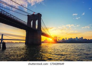 Blick auf die Brooklyn Brücke und Brooklin bei lebendigem Sonnenaufgang, New York City