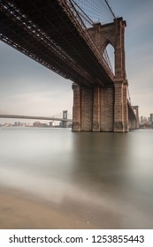 View on Brooklyn Bridge from east river sand beach at sunset with long exposure
