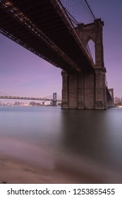 View on Brooklyn Bridge from east river sand beach at night with long exposure