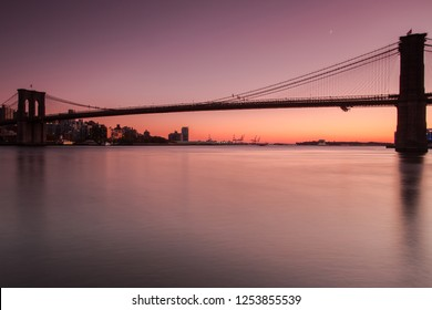 View on Brooklyn Bridge from east river at sunset with long exposure